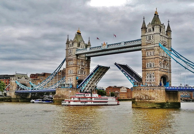 A boat going under the raised bascules of Tower bridge