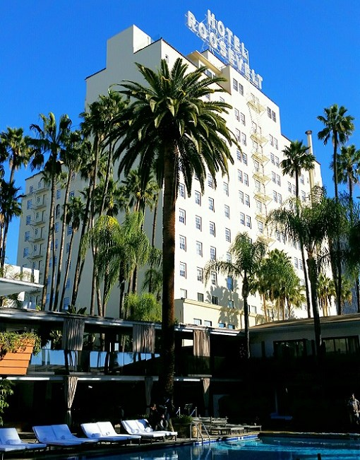 The Roosevelt Hotel behind the palm trees surrounding the pool area