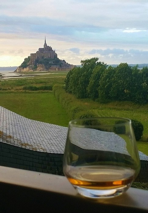 Enjoying a tipple of rum on the balcony with view of Mont St Michel in the background
