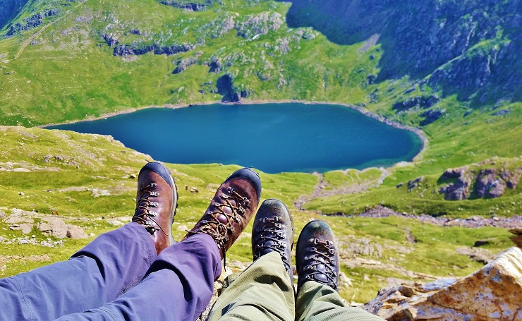 Foot selfie on the mountain top with lake below