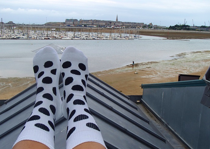 Black polka dot HappySock selfie looking over moored boats in the St Malo bay in Brittany