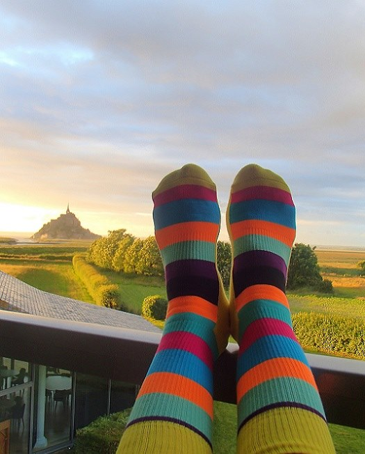 Colourful striped HappySocks Selfie on the hotel balcony with the sun setting over Mont St Michel in the distance