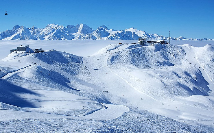 View of ski runs and mountains protruding above the clouds