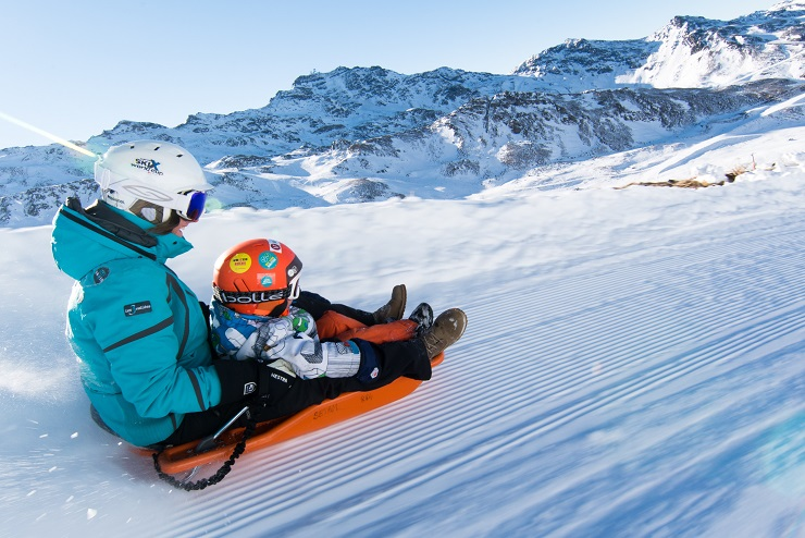 Adult and child tobogganing on the snow