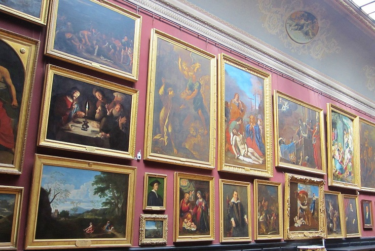 antique paintings covering the museum wall