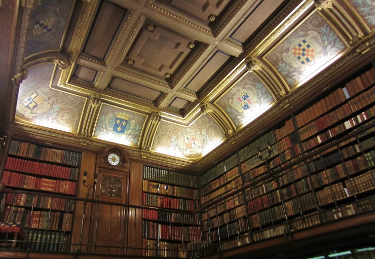 upper level bookshelves and ornate ceiling of reading room