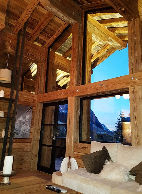 looking out of chalet windows while relaxing on the couch