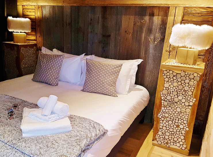 Chalet bedroom made up with towels and sweets on the bed