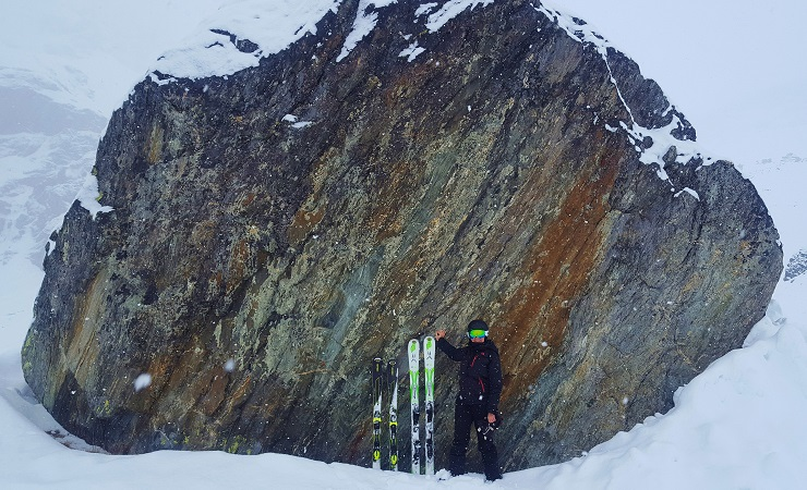 Resting with skis against large rock while it snows