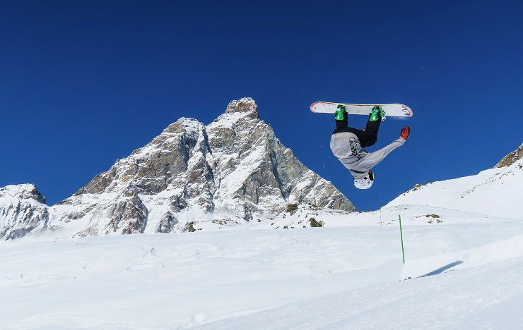 snowboarder performing backflip with Matterhorn in the background