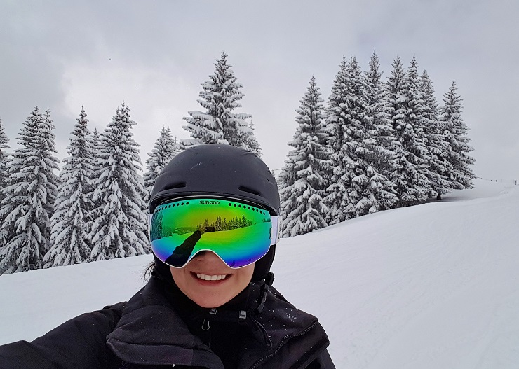 Selfie on the slopes wearing green ski goggles