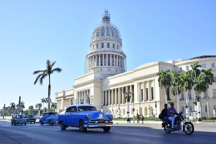 Old cars driving in front of El Capitolio, or National Capitol Building in Havana