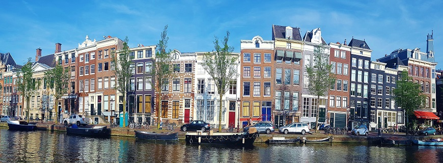 panoramic view of colourful buildings and boats on the canal