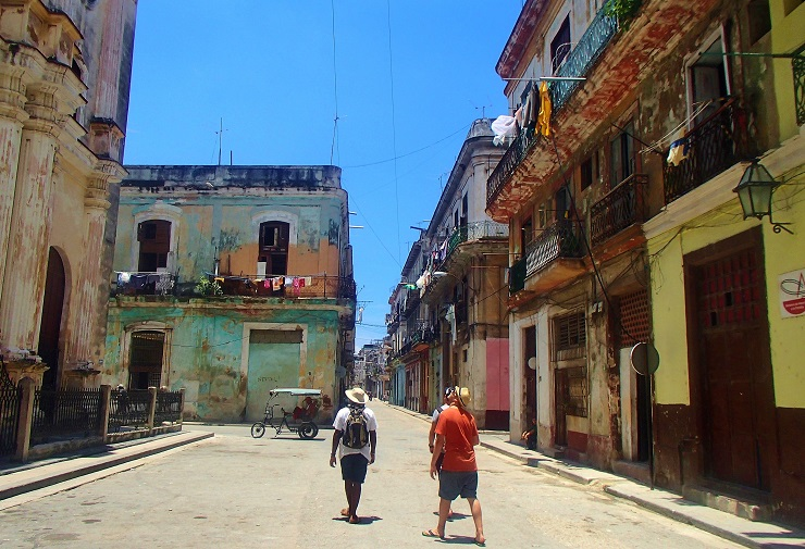 tourists wandering along the streets past aged buildings of Havana old town.