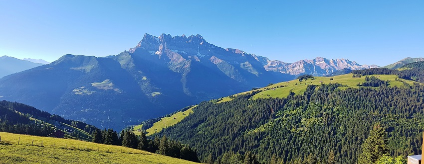 Panoramic view of Dents du Midi with green rolling hills in foreground