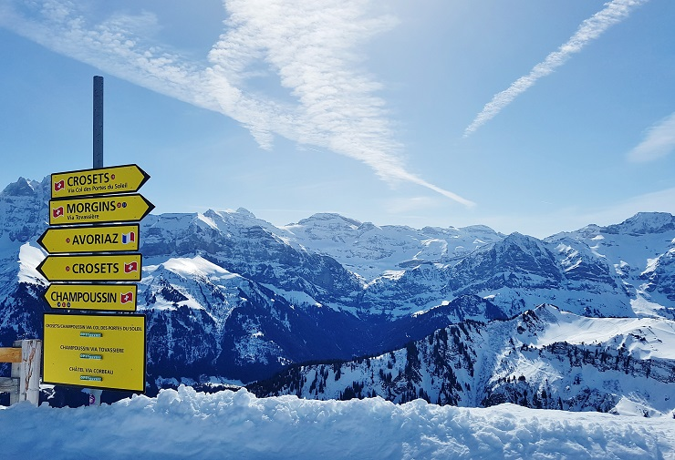 Ski run signpost at the France-Switzerland border with Alps in the background