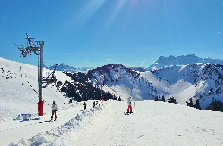 Sunny day on the ski fields with skiers on the drag lift