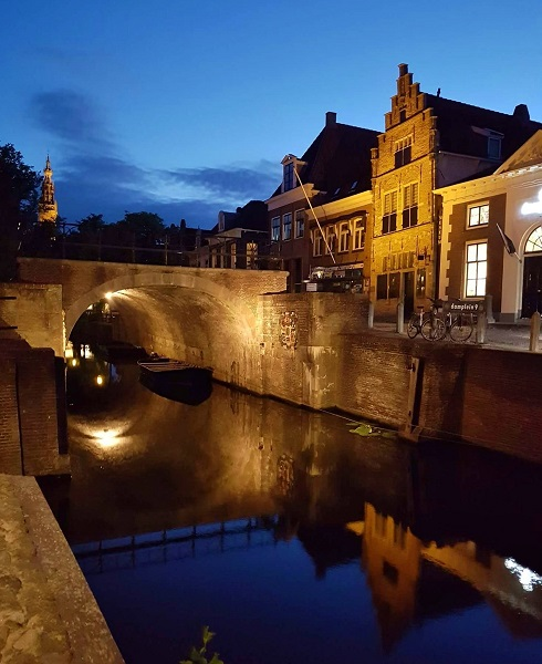 Canal bridge and building lit up at night Edam Netherlands