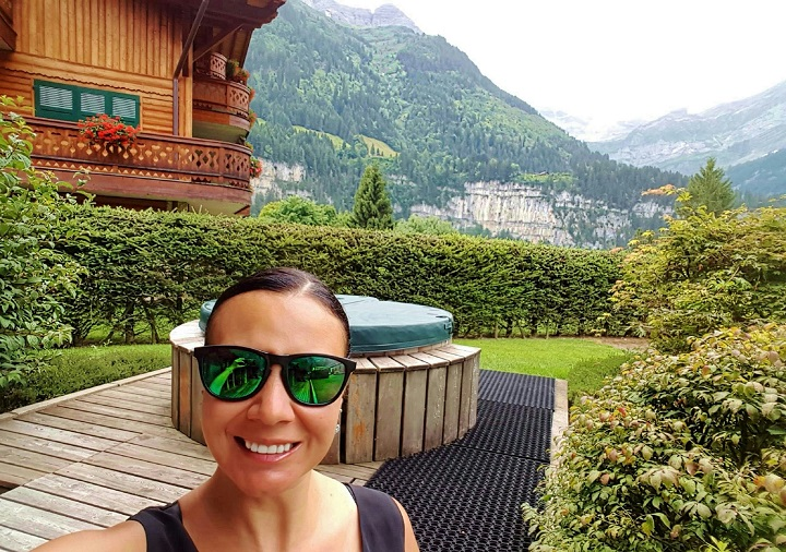 Mel in front of hot tub showing the mountain views