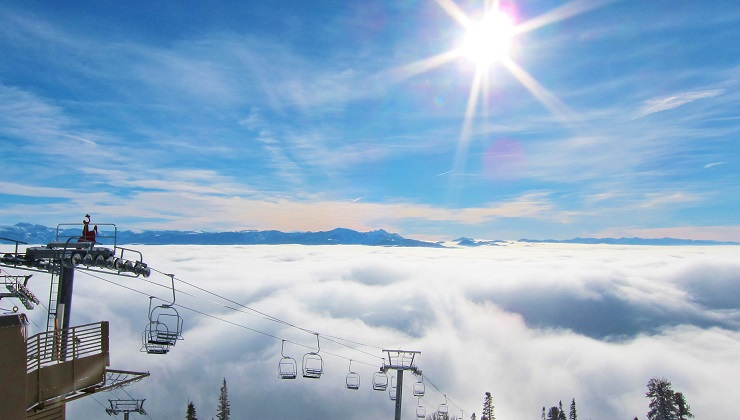 Chairlift rising above the clouds