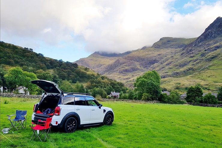 The Mini cooper in the campsite with mountains in the background