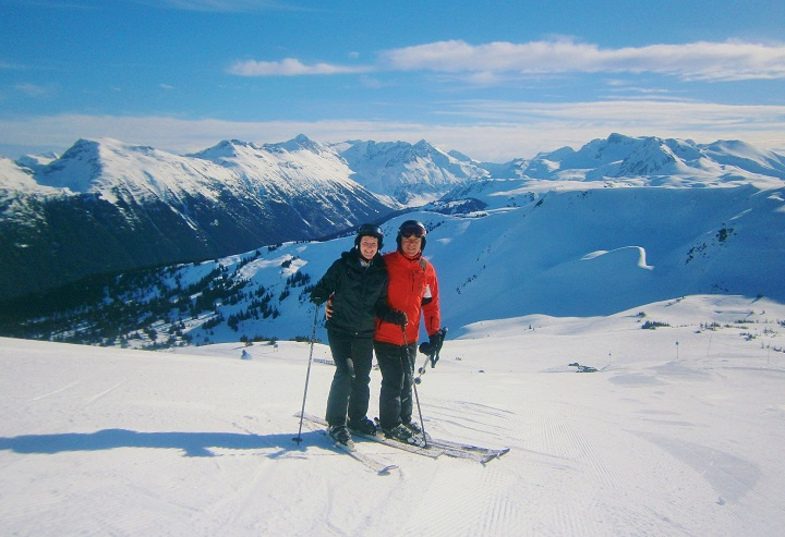 Couple stopped for a picture on the top of Whistler Ski Resort Canada