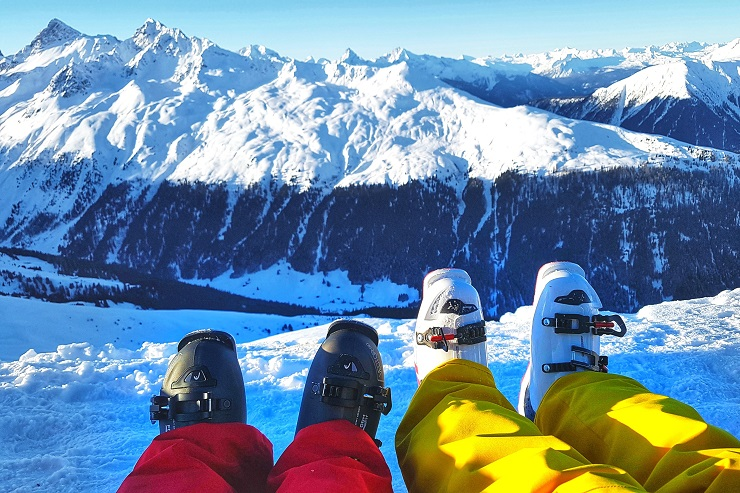 Picture of skiers boots while resting in the snow admiring the view of the snow covered mountains