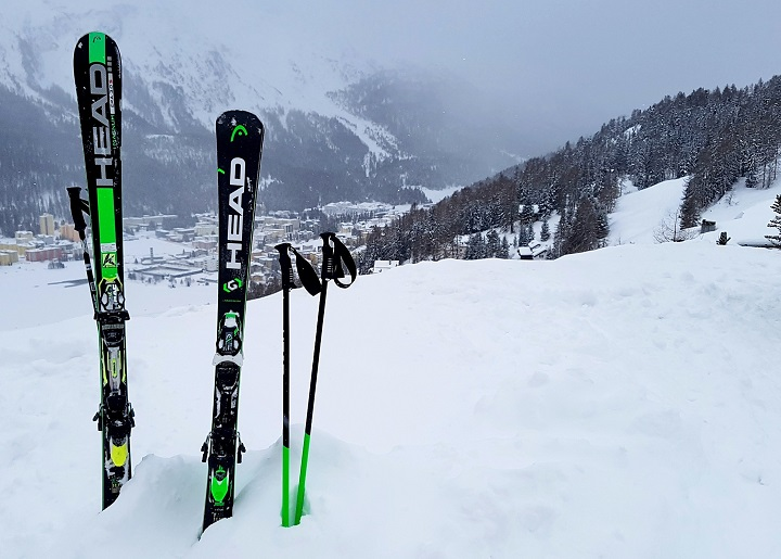Head skis standing in the snow with St Moritz in the background