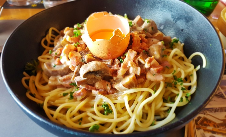 Carbonara topped with egg yolk in its shell