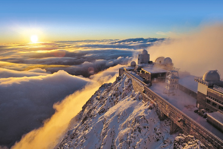 Pic du Midi observatory above the clouds with the sun rising in the distance