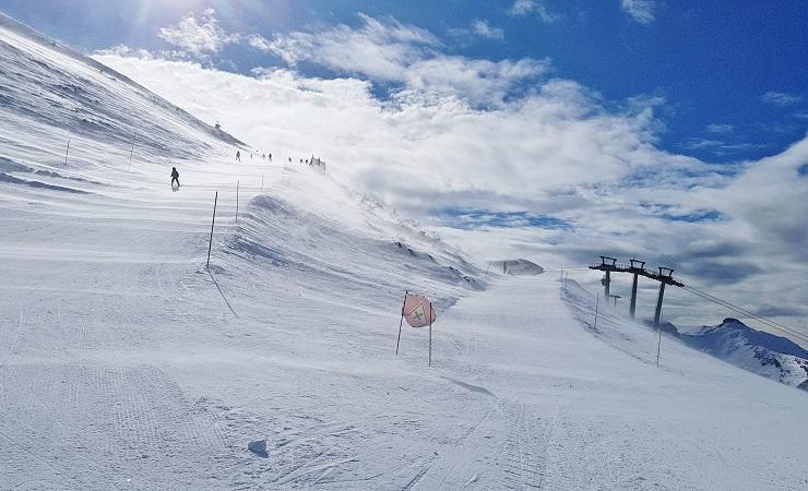 Wind sweeping snow across the ski runs