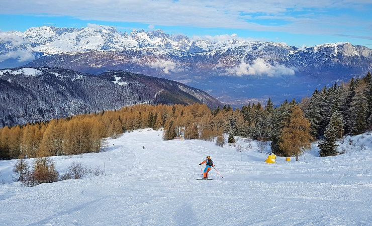 Skiing towards the forested area with the Dolomites in the background