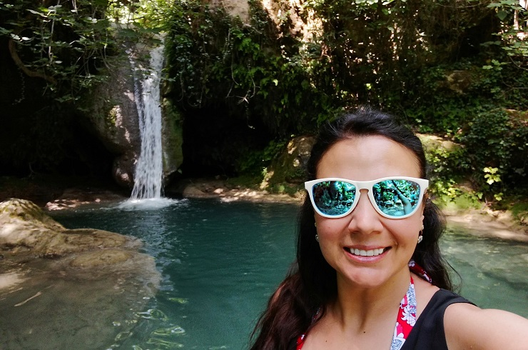 Selfie with waterfall cascading into blue pool of water in the background