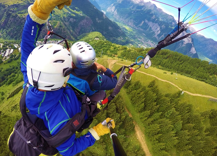 Selfie view while paragliding over green fields in Alpe d'Huez