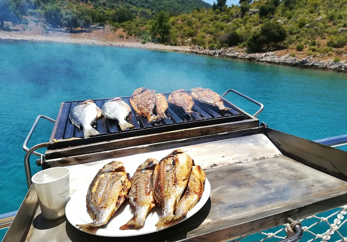 Whole fish grilling on the boat's barbecue