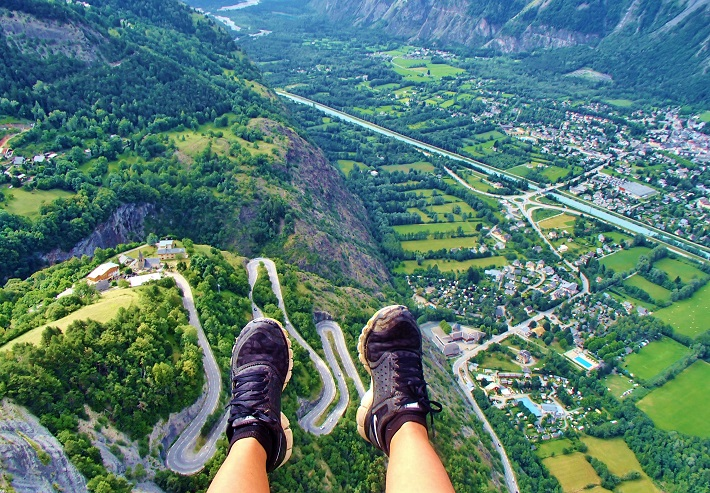 Foot picture while gliding over the hairpin bends and city in the valley