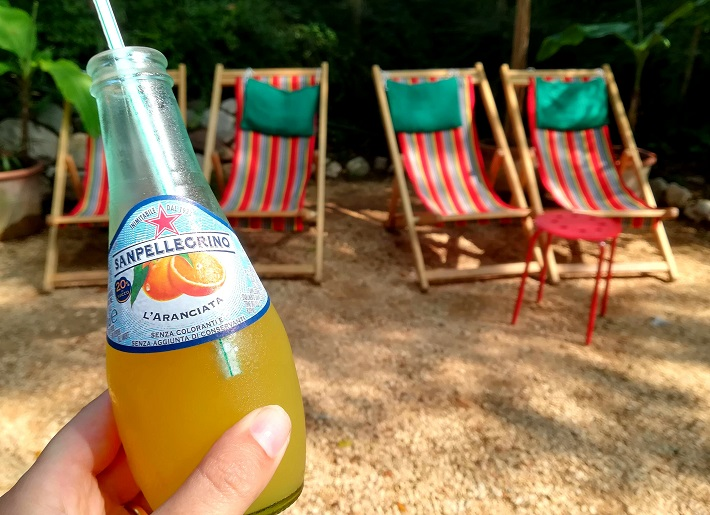 A refreshing orange drink with deck chairs in the background