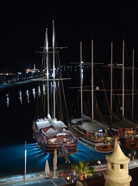 Sail boats moored on the marina at night