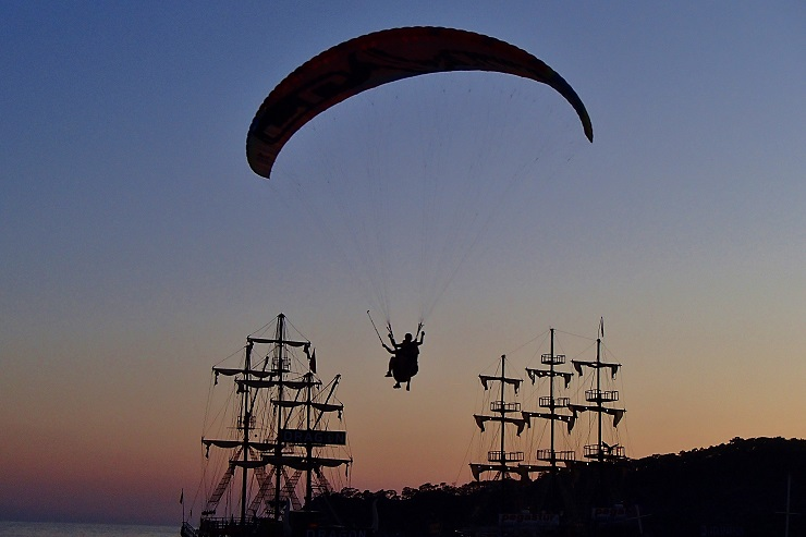 Silhouette of a Paraglider between the masts of two ships