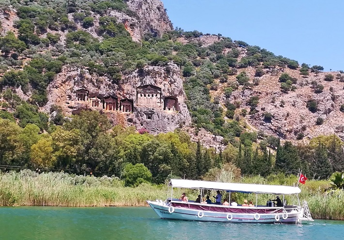 Tour boat sailing past the Lycian Tombs carved into the mountain rock face.