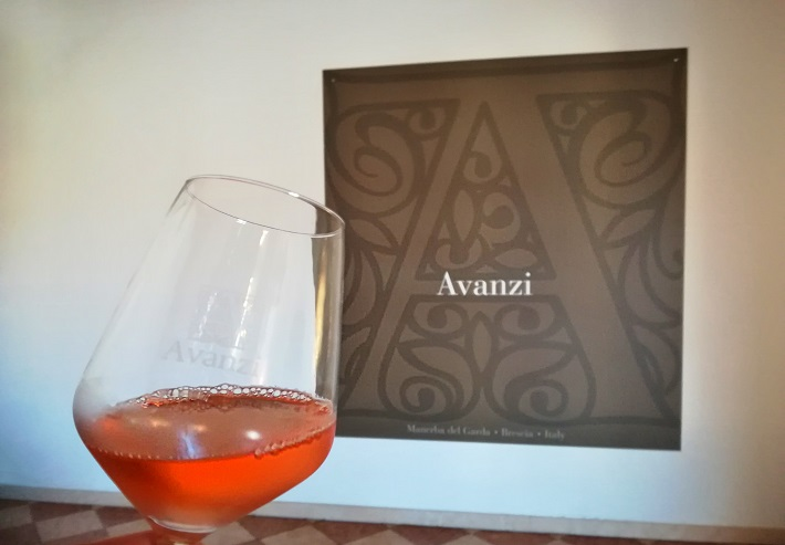 A glass of Rosé in front of Avanzi sign
