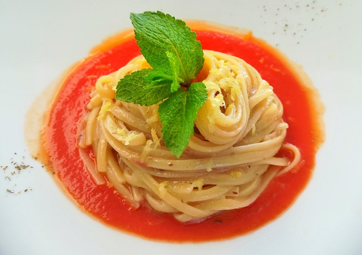 Pasta with red sauce topped with fresh mint
