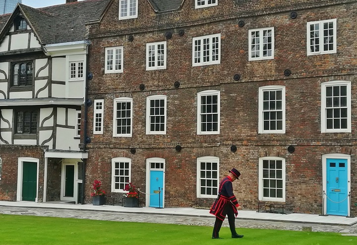 Yeoman warder walking across the grass in front of buildings inside the Tower of London