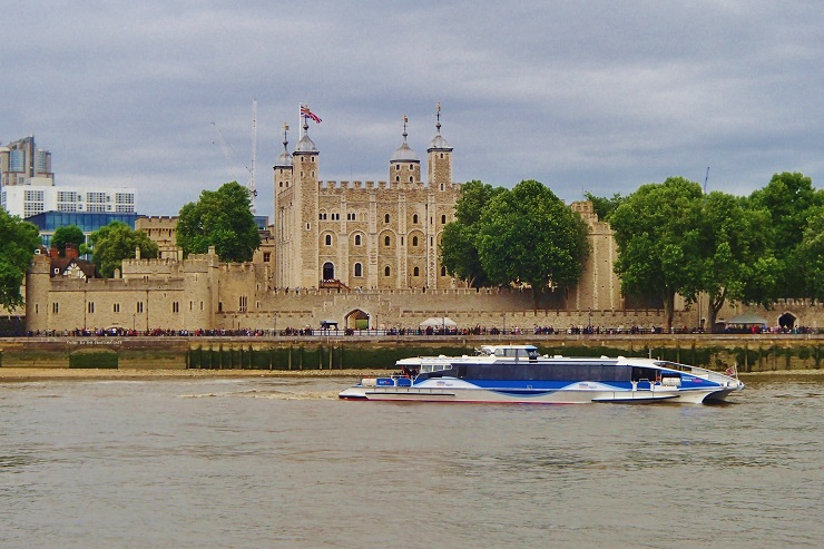 View of Tower of London across the Thames with a Thames riverboat sailing past