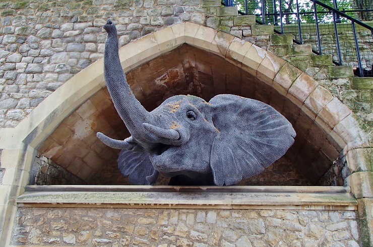 Wire statue of an elephant looking out of an enclosed archway
