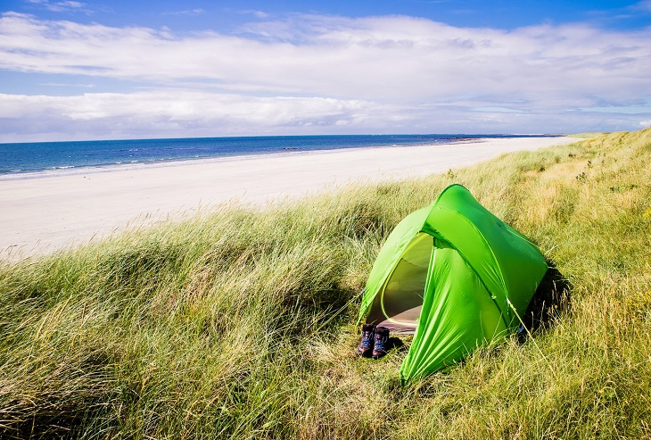 Green tent on the deserted beach