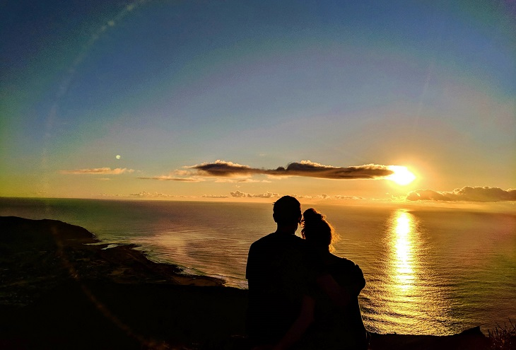 Silhouette of couple on cliff watching the sunset