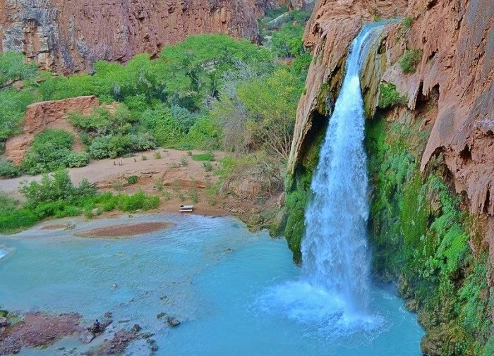 Waterfall cascading into turquoise pool
