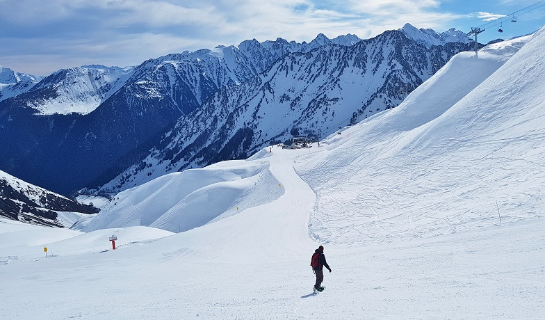 Lone snowboarder making his way down a run at Cauterets ski resort - French Pyrenees