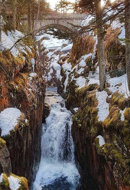 Small waterfall running under a stone arch bridge